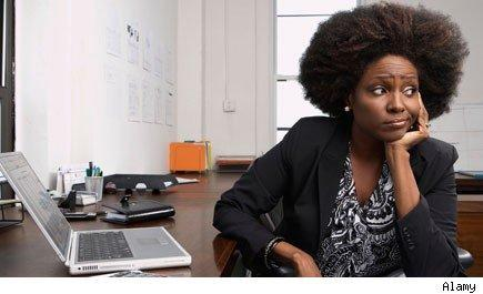 frowning female office worker with chin resting on hand