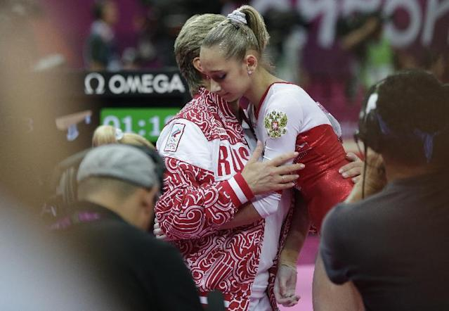 Russian gymnast Victoria Komova is consoled by a team official after a performance during the Artistic Gymnastics women's team final at the 2012 Summer Olympics, Tuesday, July 31, 2012, in London. (AP Photo/Julie Jacobson)