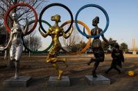 Child plays football near a statue of Olympic rings at the Olympic Forest Park in Beijing