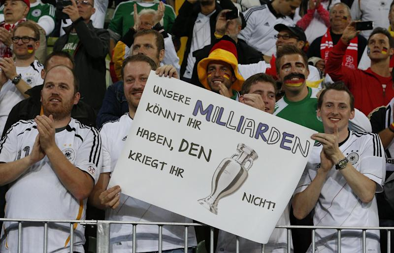 German fans hold a poster reading 'You can have our billions but you won't get the trophy' after Germany won the Euro 2012 soccer championship quarterfinal match between Germany and Greece in Gdansk, Poland, Friday, June 22, 2012. (AP Photo/Michael Sohn)