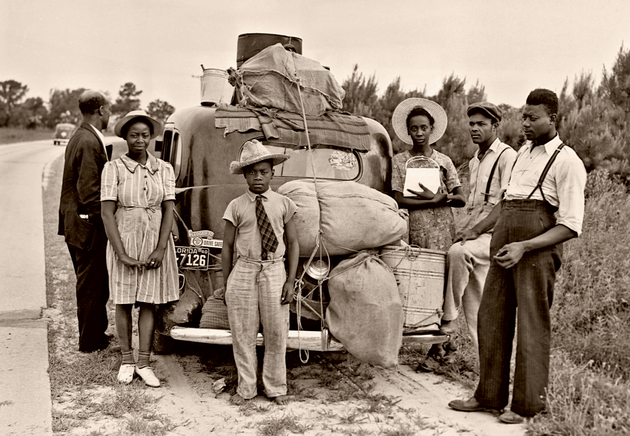 Migrant workers from Florida take a roadside break in Shawboro, North Carolina, on their way to pick potatoes in New Jersey, circa July 1940.