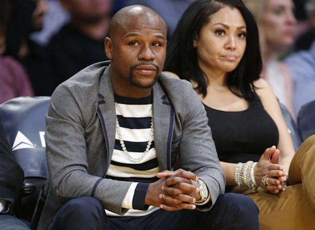 Boxer Floyd Mayweather Jr. and Jamie Lynn sit courtside as they attend the NBA basketball ball game between the Los Angeles Lakers and Washington Wizards. (AP Photo/Danny Moloshok)