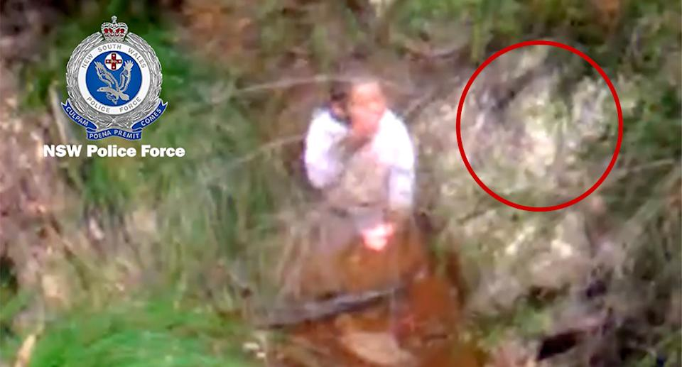 Rescue helicopter image of the boy sipping water from a creek.