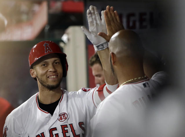 Los Angeles Angels' Andrelton Simmons, left, celebrates his solo home run with teammate Albert Pujols during the third inning of a baseball game against the Houston Astros, Monday, July 15, 2019, in Anaheim, Calif. (AP Photo/Marcio Jose Sanchez)