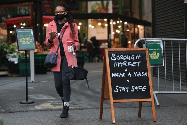A shopper passes a coronavirus advice sign at Borough Market, London, which became the first outdoor space in the UK to legally enforce the wearing of face masks for all customers and stallholders