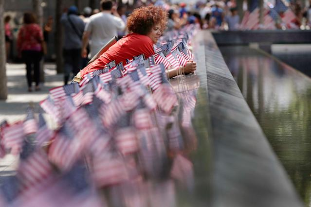 <p>A woman pauses among American flags that were inserted in each of the 2.983 names on the borders of the reflecting pools of the 9/11 Memorial, in New York, Tuesday, July 4, 2017. (Photo: Richard Drew/AP) </p>