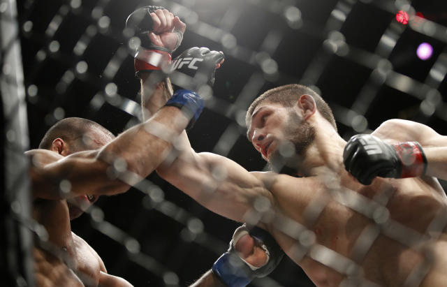 Khabib Nurmagomedov (R) takes a swing at Edson Barboza at UFC 219 on Dec. 30, 2017, in Las Vegas. (AP Photo)