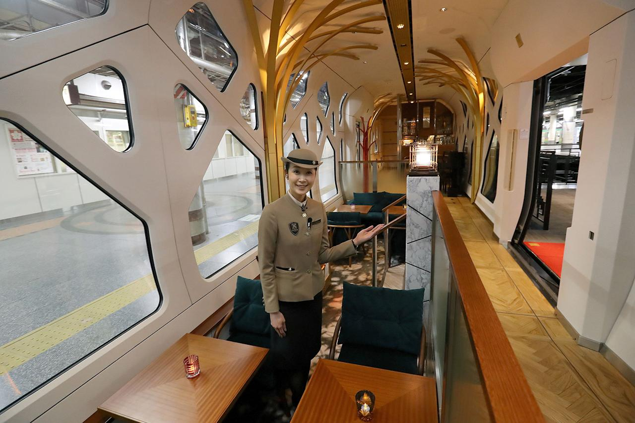 <p>A crew member shows the lounge car aboard the Train Suite Shiki-shima during a press preview in Tokyo. (Photo: STR/AFP/Getty Images) </p>