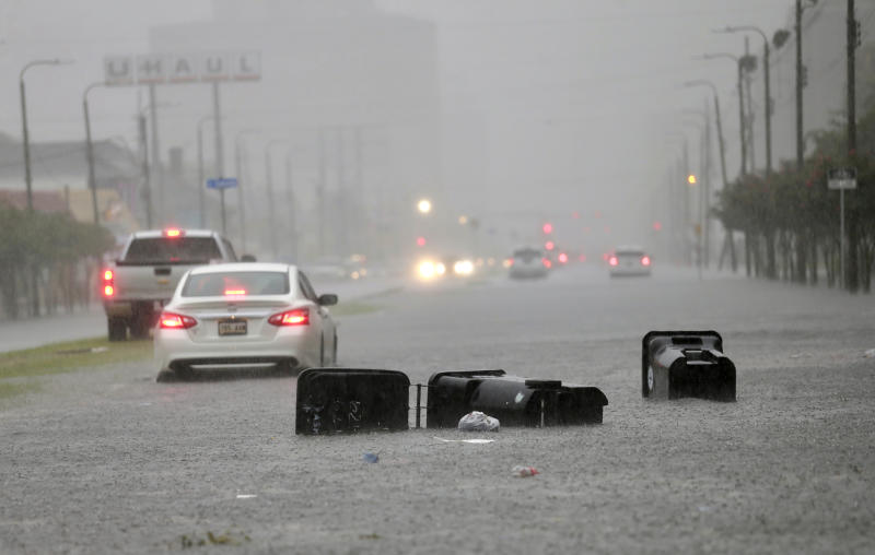 Vehicles head down a flooded Tulane Ave. as heavy rain falls Wednesday, July 10, 2019, in New Orleans. (David Grunfeld/The Advocate via AP)