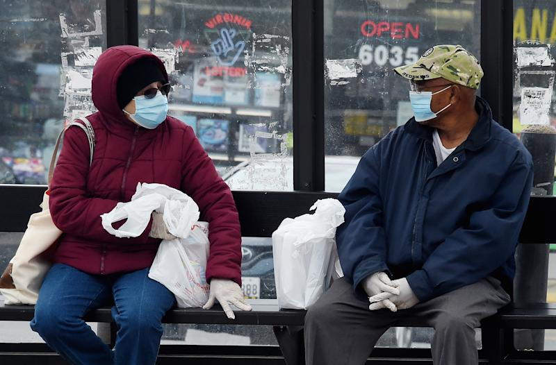People wearing face masks wait for their bus amid the coronavirus pandemic on May 14, 2020 in Arlington, Virginia. - Over a third of US workers who lost jobs or saw their hours reduced because of the coronavirus pandemic will have trouble paying their bills and nearly half do not have an extra $400 for an emergency, according to a survey released Thursday. (Photo by Olivier DOULIERY / AFP) (Photo by OLIVIER DOULIERY/AFP via Getty Images)