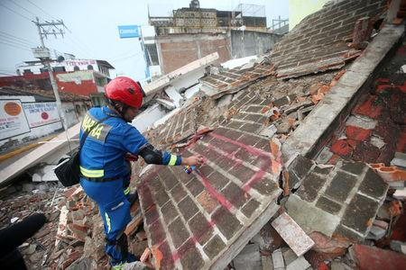 A rescue worker marks debris in the city of Juchitan, after an earthquake struck the southern coast of Mexico late on Thursday, in Mexico September 10, 2017. REUTERS/Edgard Garrido