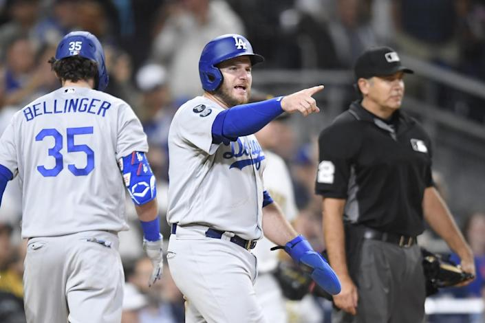 Dodgers' Max Muncy points out to Justin Turner after scoring.