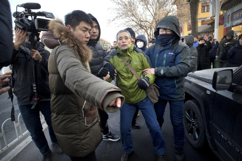 Plainclothes security officers take away a supporter of Chinese human rights lawyer Wang Quanzhang near the Secondary Intermediate People's Court of Tianjin northeastern China's Tianjin municipality, Wednesday, Dec. 26, 2018. The trial of Wang, who was charged with subversion of state power in 2016, was expected to begin at the court on Wednesday morning. (AP Photo/Mark Schiefelbein)