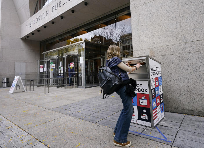 """Voter Linda Borman drops her ballot into the ballot box outside the Boston Public Library, Monday, Oct. 26, 2020, in Boston. Massachusetts election officials say a fire was set in the ballot drop box, Sunday, holding more than 120 ballots in what appears to have been a """"deliberate attack."""" The FBI says it is investigating. (AP Photo/Elise Amendola)"""