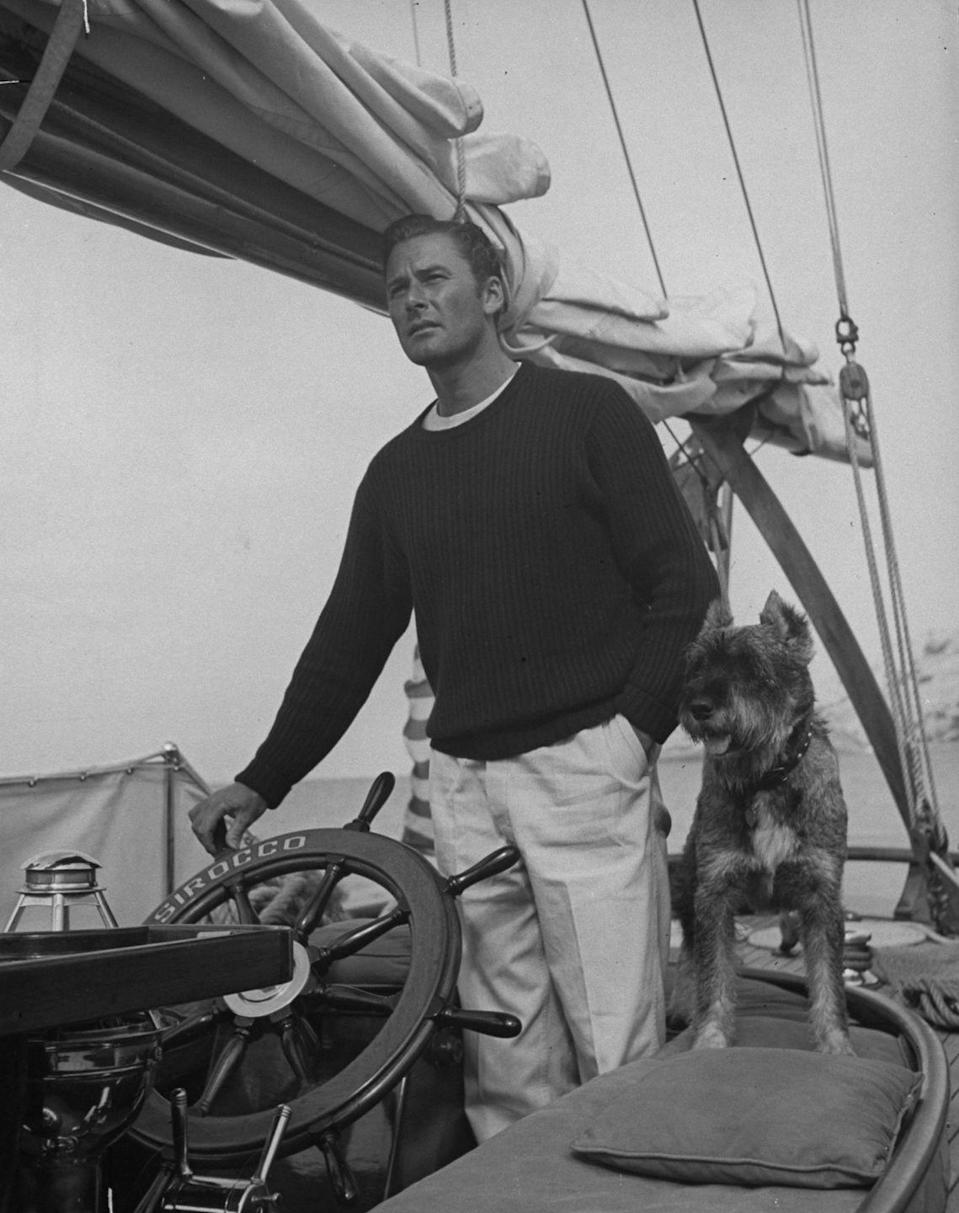 <p>Actor Errol Flynn with his dog at the helm of a yacht while enjoying a fishing vacation, circa 1941.</p>