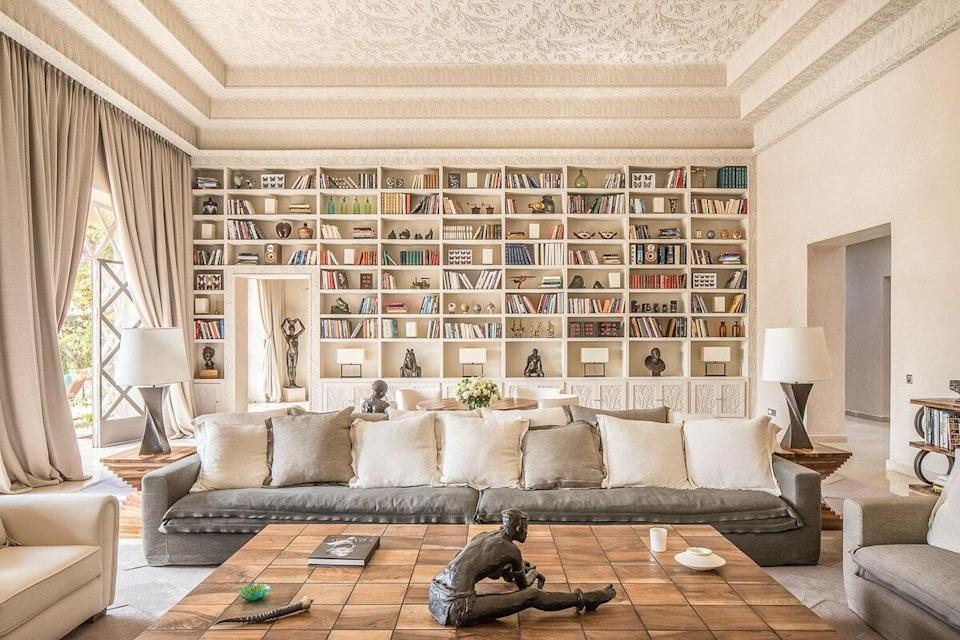 """This is the one Airbnb in this gallery that isn't a Superhost, but it is a price-upon-request <a href=""""https://www.cntraveler.com/story/airbnb-luxe-a-first-look?mbid=synd_yahoo_rss"""" rel=""""nofollow noopener"""" target=""""_blank"""" data-ylk=""""slk:Airbnb Luxe"""" class=""""link rapid-noclick-resp"""">Airbnb Luxe</a>, which come with a trip designer who can help organize airport transfers, kitchen pre-stocks, childcare, and more. This particular six-bedroom villa already includes a cook, driver, head of staff, and two maids so you won't have to lift a finger during your stay. While the bookshelves in the neutral living room wows, the oasis-style pool, tiled fireplaces in each bedroom, colorful kids playroom, and vintage cars put a stay here over the top."""