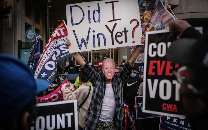 A supporter of President Donald J. Trump wears a mask of vice-president Joe Biden as he attends a protest outside the vote counting center in Philadelphia, Pennsylvania - Shutterstock