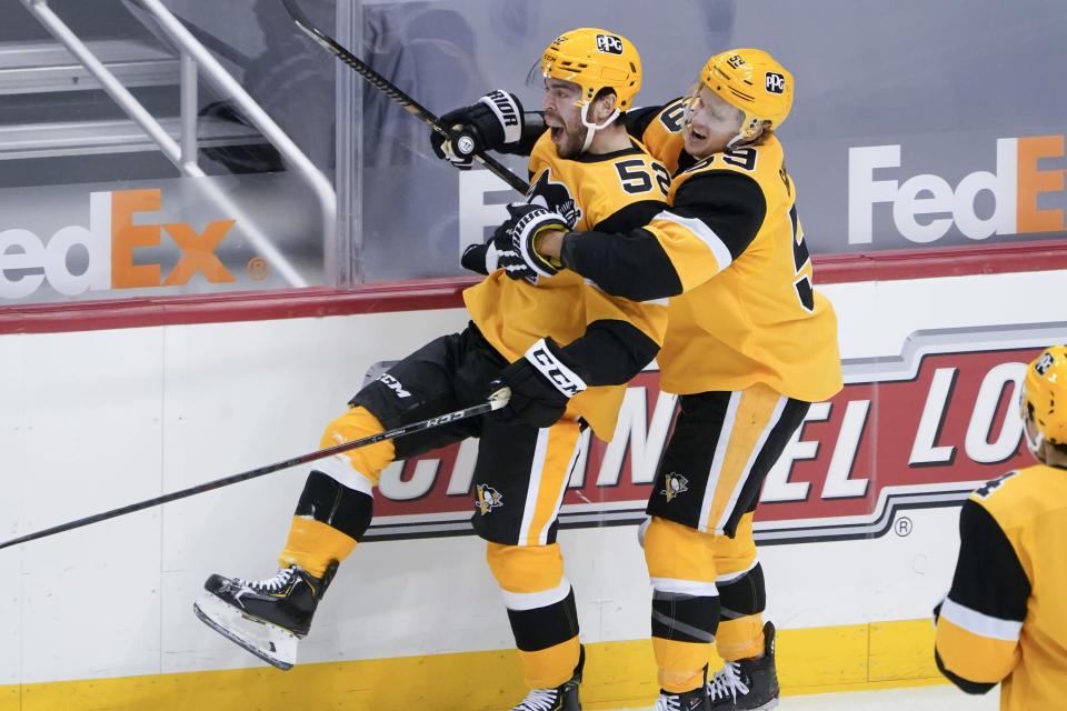 Pittsburgh Penguins' Mark Friedman, left, celebrates with Jake Guentzel after his first NHL goal, during the first period of the team's hockey game against the Philadelphia Flyers, Thursday, March 4, 2021, in Pittsburgh. (AP Photo/Keith Srakocic)