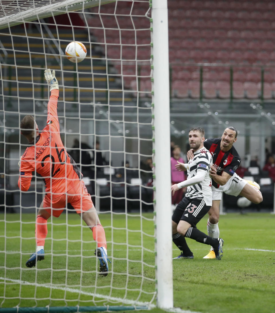 Manchester United's goalkeeper Dean Henderson, left, deflects a shot away from the goal from AC Milan's Zlatan Ibrahimovic, right, during the Europa League round of 16 second leg soccer match between AC Milan and Manchester United at the San Siro Stadium, in Milan, Italy, Thursday, March 18, 2021. (AP Photo/Antonio Calanni)