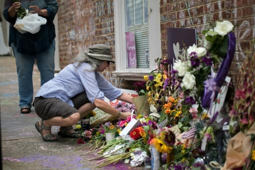 A woman places flowers on a makeshift memorial dedicated to Heather Heyer in downtown Charlottesville, Virginia, one year after the violent white nationalist rally where Heyer was killed and dozens of others were injured