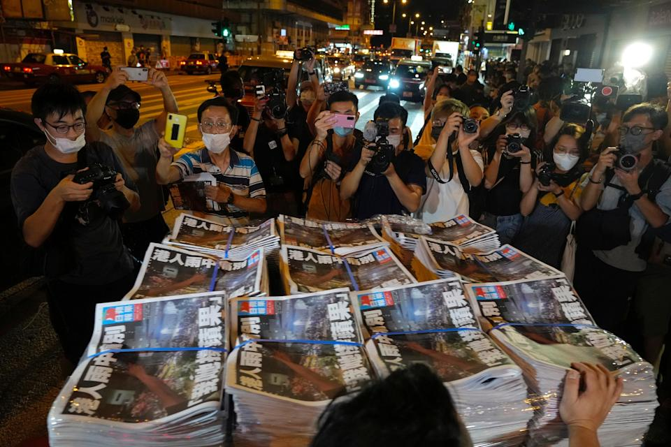 People gather to buy the last issue of Apple Daily as it arrives at a newspaper booth in Hong Kong, early Thursday (AP)