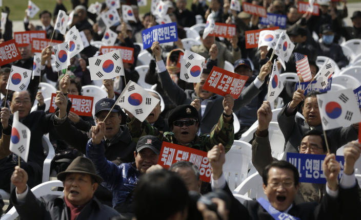 """South Korean protesters shout slogans during a rally to mark the third anniversary of the sinking of South Korean naval ship """"Cheonan"""" which killed 46 South Korean sailors, in Seoul, South Korea, Tuesday, March 26, 2013. An explosion ripped apart the 1,200-ton warship, killing 46 sailors near the maritime border with North Korea in 2010. The placards read: """"Punishment, North Korea's provocation."""" (AP Photo/Lee Jin-man)"""