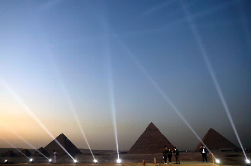 FILE PHOTO: People take pictures in front of the Great Pyramids in Giza