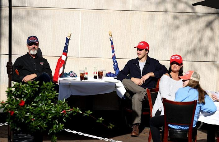 "Supporters of U.S. President Donald Trump sit at a restaurant during the ""Million MAGA March"" from Freedom Plaza to the Supreme Court, on November 14, 2020 in Washington, DC. Supporters of U.S. President Donald Trump marching to protest the outcome of the 2020 presidential election. (Photo by Tasos Katopodis/Getty Images)"