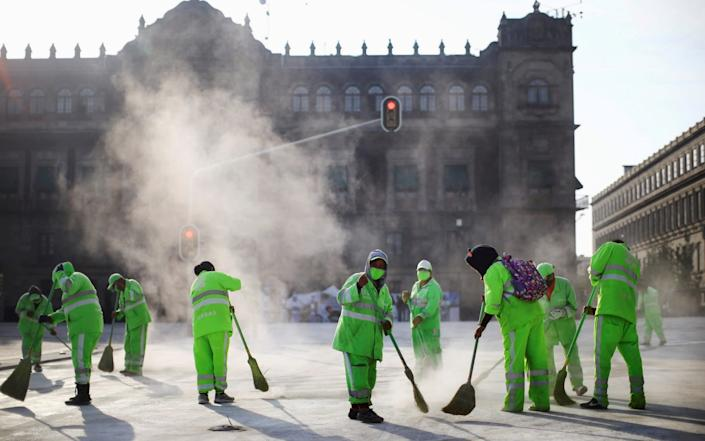 Municipal employees work in a cloud of dust at Zocalo square in Mexico City - REUTERS/Edgard Garrido