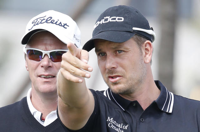 Henrik Stenson of Sweden, right, talks with his caddie at the 1st hole during a pro-am competition ahead of the Masters golf tournament at the Lake Malaren Golf Club in Shanghai, China, Wednesday, Oct. 23, 2013. The Shanghai Masters will begin on Oct. 24. (AP Photo/Eugene Hoshiko)