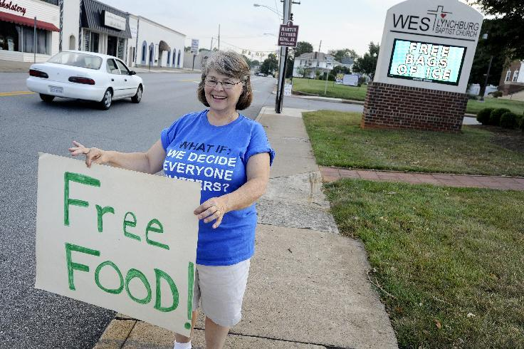 Phyllis Lane waves a sign for passing motorists advertising a free meal sponsored by West Lynchburg Baptist Church in Lynchburg, Va., Wednesday, July 4, 2012. The church regained power Tuesday and has since opened its doors as a cooling shelter, offering a place for people to relax, sleep and eat. (AP Photo/The News & Advance, Parker Michels-Boyce)
