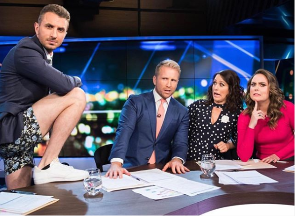 Tommy Little wearing a shirt, suit and jacket with short floral shorts on set of The Project while his co-hosts look on in shock