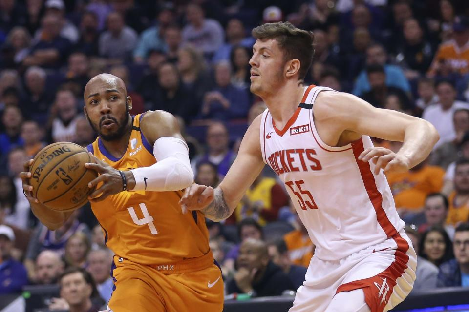 Phoenix Suns guard Jevon Carter (4) drives past Houston Rockets center Isaiah Hartenstein (55) during the second half of an NBA basketball game Friday, Feb. 7, 2020, in Phoenix. The Suns won 127-91. (AP Photo/Ross D. Franklin)