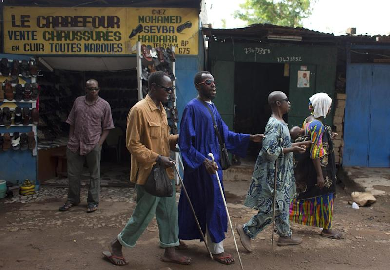 A woman leads a group of three blind men, singing as they beg, through a market area in central Bamako, Mali, Friday, Aug. 2, 2013. Mali's presidential race will go to a second round on Aug. 11. Candidate Ibrahim Boubacar Keita finished with a strong lead over his next closest rival, Soumaila Cisse, but still well shy of the majority needed to win outright in the first round.(AP Photo/Rebecca Blackwell)