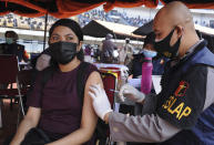 A woman receives a shot of the Sinovac COVID-19 vaccine during a mass vaccination at a soccer stadium in Bandung, West Java, Indonesia, Thursday, June 17, 2021. Indonesia's president ordered authorities to speed up the country's vaccination campaign as the World Health Organization warned Thursday of the need to increase social restrictions in the country amid a fresh surge of coronavirus infections caused by worrisome variants. (AP Photo/Bukbis Candra)