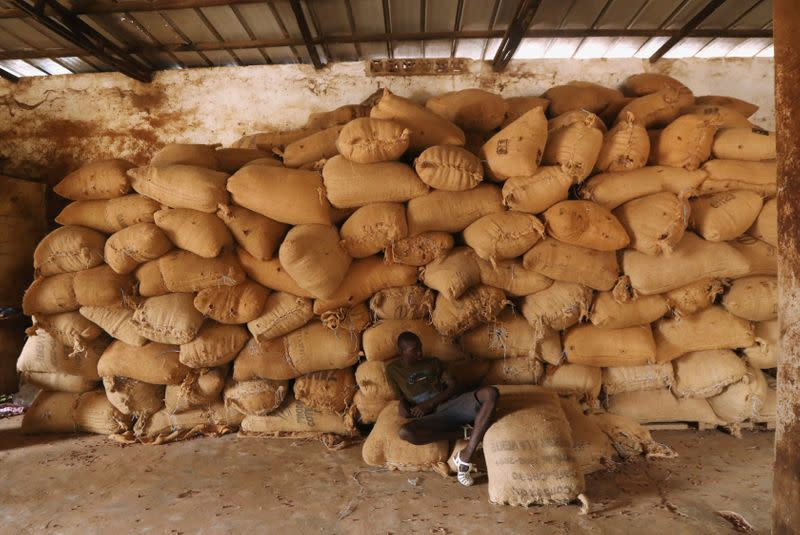 A worker sits near a pile of sacks of cocoa at a warehouse in Soubre,