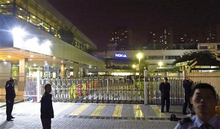 Police and security guards stand outside a gate of the Nokia factory during a protest of around one hundred factory workers in Dongguan