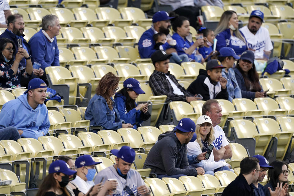 Several fans are seen without masks as they watch the Miami Marlins play the Los Angeles Dodgers in a baseball game Friday, May 14, 2021, in Los Angeles. The U.S. Centers for Disease Control and Prevention eased its guidelines on the wearing of masks outdoors, saying fully vaccinated Americans don't need to cover their faces anymore unless they are in a big crowd of strangers. (AP Photo/Mark J. Terrill)