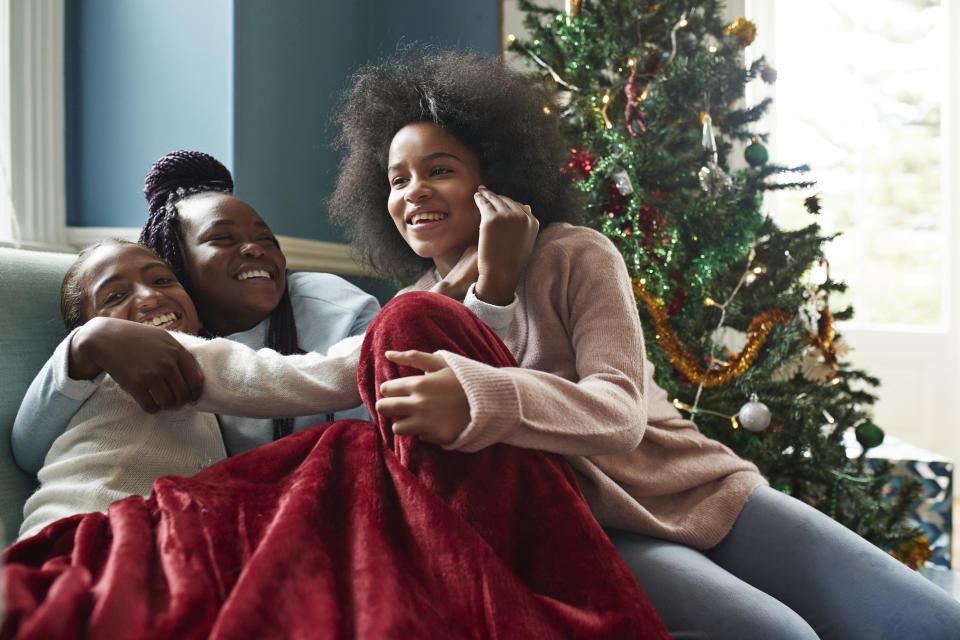Happy sisters embracing while sitting on sofa by Christmas tree at home