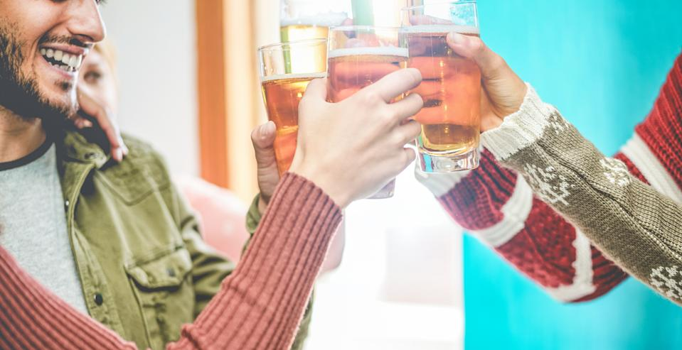 Group of friends cheering with beers in pub restaurant - Young people having fun drinking and toasting on happy hour at trendy bar - Friendship and youth concept - Focus on close-up glasses