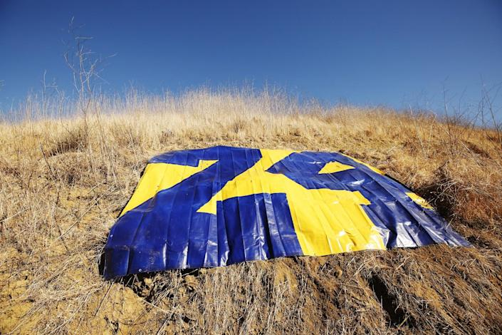 A large plastic tarp shows Kobe Bryant's number 24 in purple and gold
