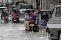 A woman wearing a mask to prevent the spread of the coronavirus rides a motorcycle as they pass a flooded street due to Typhoon Molave in Pampanga province, northern Philippines on Monday, Oct. 26, 2020. A fast moving typhoon has forced thousands of villagers to flee to safety in provinces. (AP Photo/Aaron Favila)