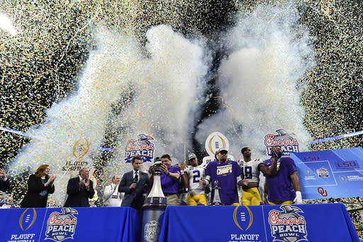 LSU coach Ed Orgeron and team celebrate winning the Peach Bowl NCAA semifinal college football playoff game against Oklahoma, Saturday, Dec. 28, 2019, in Atlanta. LSU won 63-28. (AP Photo/John Amis)