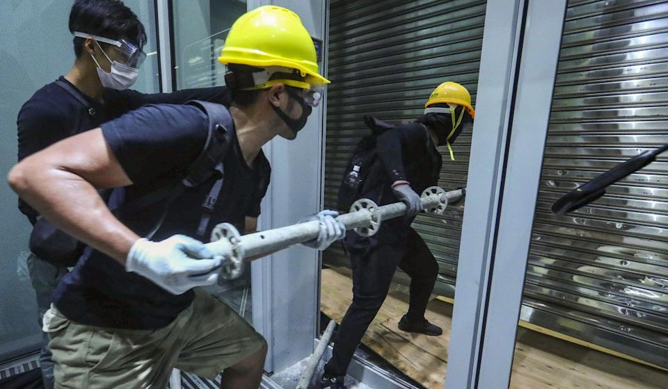 Protesters batter the security shutters at Legco. Photo: Edmond So