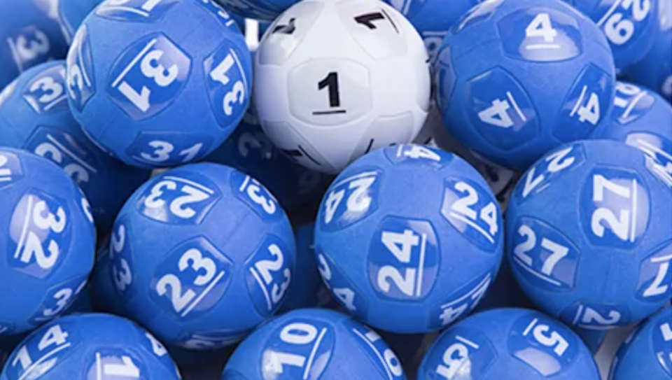 The white Powerball is nestled among other blue lottery balls.