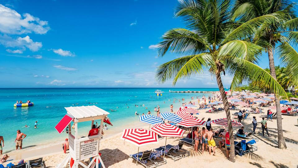 People enjoy Doctor's Cave Beach, a famous, white, sandy beach in Montego Bay Jamaica on a sunny day.