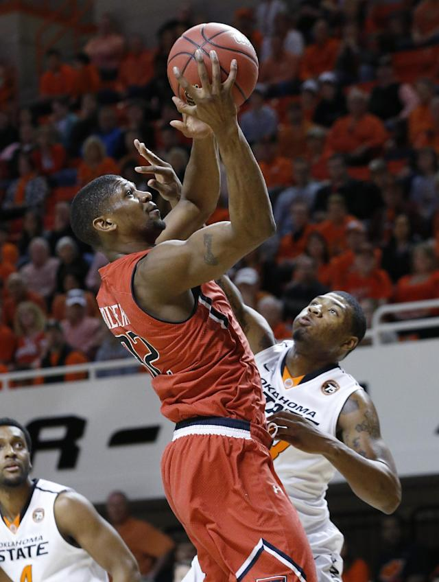 Texas Tech forward Jordan Tolbert, left, shoots in front of Oklahoma State guard Marcus Smart in the first half of an NCAA college basketball game in Stillwater, Okla., Saturday, Feb. 22, 2014. (AP Photo/Sue Ogrocki)