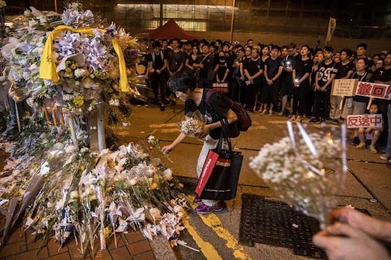 Demonstrators queued to leave flowers and tributes at the site where a protester died after falling from a building where he had been holding an hours-long anti-extradition protest (AFP Photo/DALE DE LA REY)