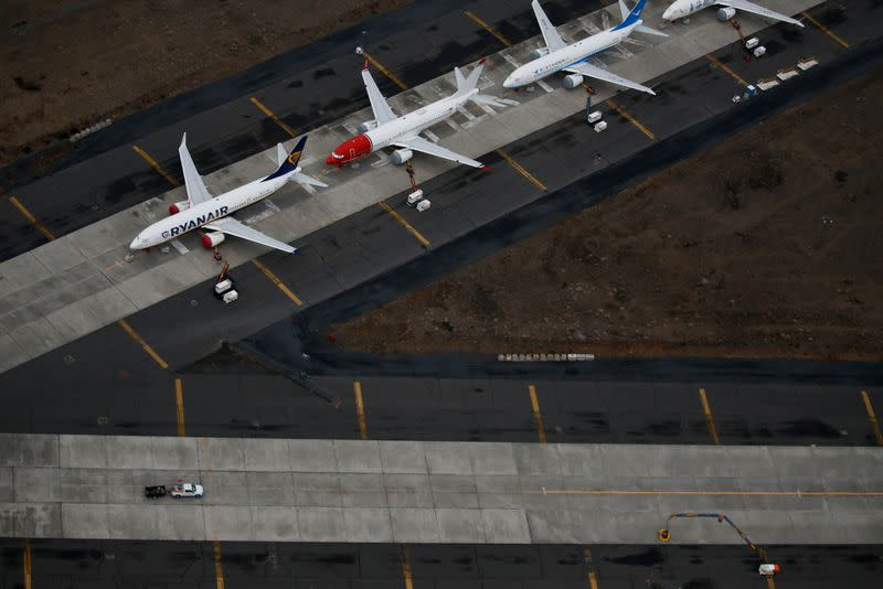 A truck drives by a line of grounded Boeing 737 MAX aircraft parked at Grant County International Airport in Moses Lake