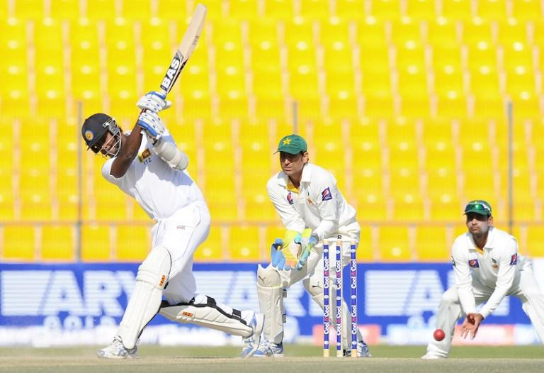 Sri Lankan batsman Angelo Mathews (L) plays a shot watched by Pakistan wicketkeeper Younis Khan (C) during the final day of the first cricket Test match between Pakistan and Sri Lanka at the Sheikh Zayed Stadium in Abu Dhabi on January 4, 2014. AFP PHOTO/Ishara S. KODIKARA